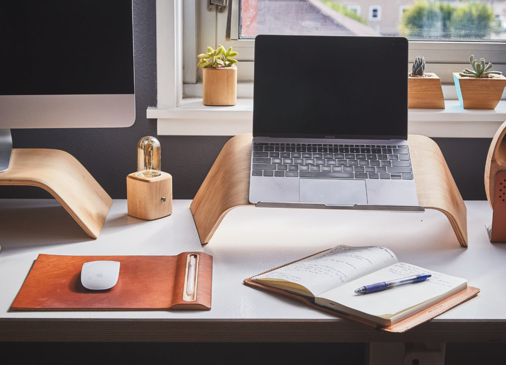 A laptop and notebook on a smooth wooden themed desk with desk accessories