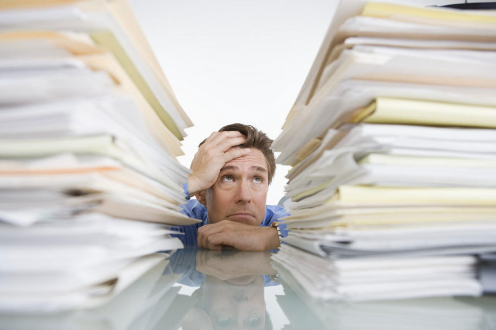 sustainable-office-ideas-man-inbetween-piles-of-papers