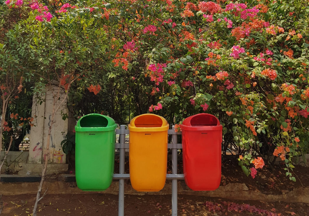 sustainable office ideas colour coded recycling bins against flower hedge
