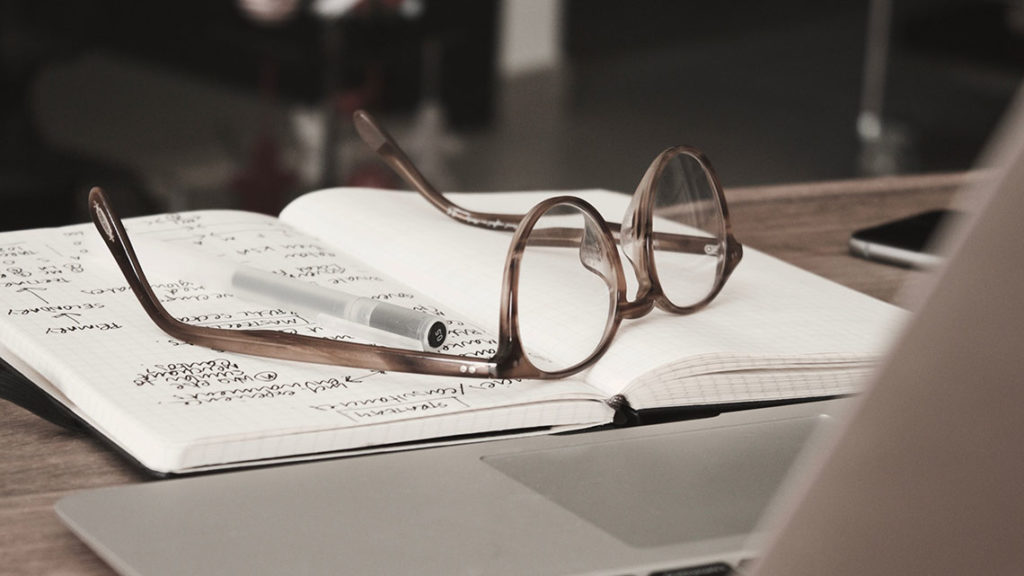 glasses and a pen on an open notebook remote working