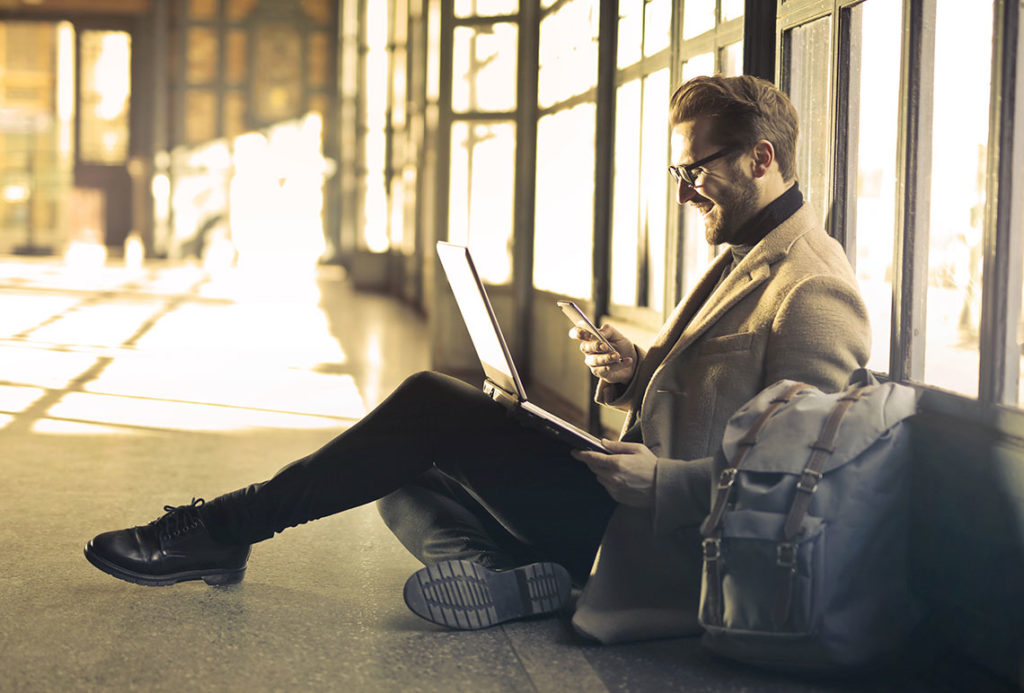 man sitting on the floor with a laptop and phone remote working