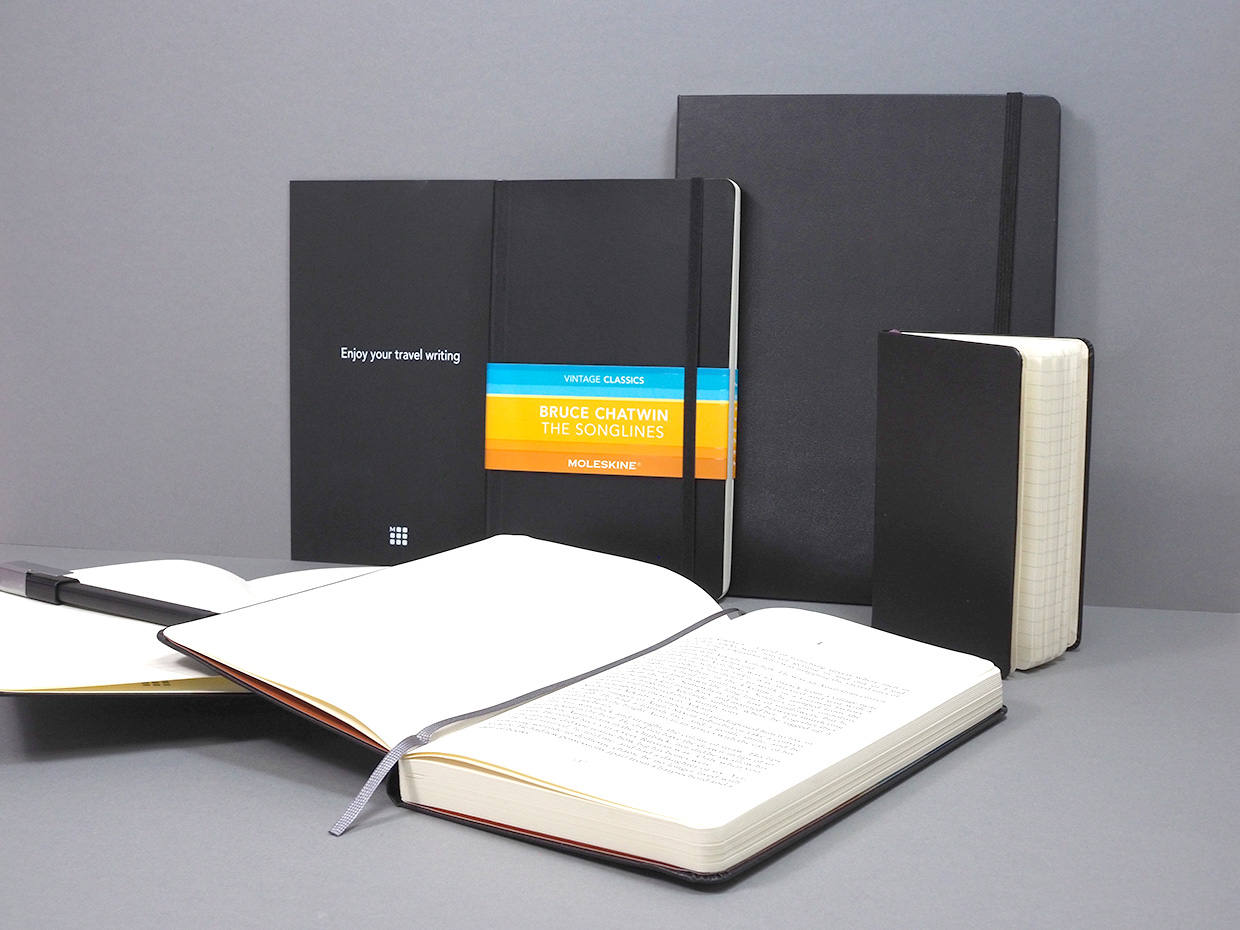 """A moleskine pocket, classic and XL notebook with a moleskine book of Bruce Chatwin's """"The Songlines""""."""